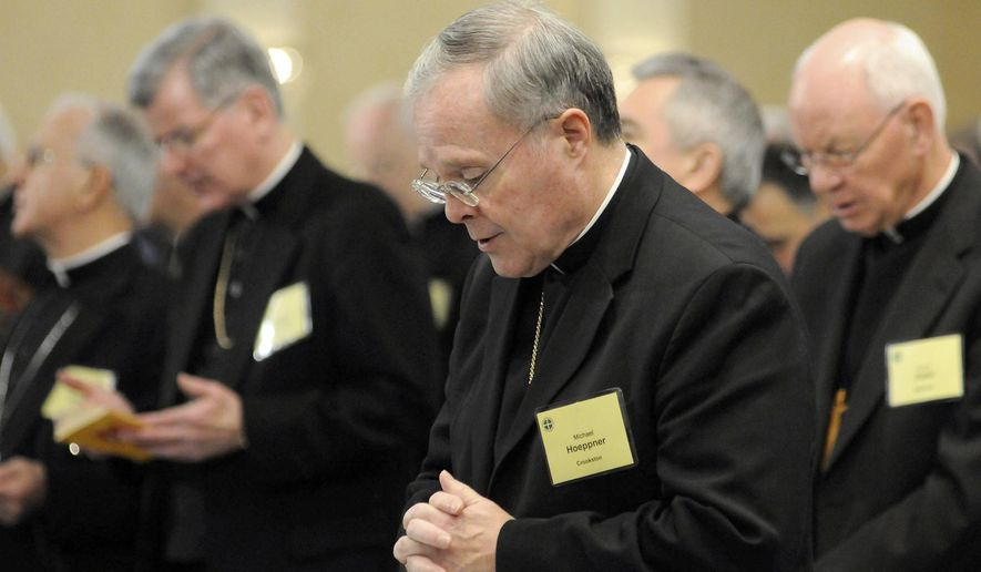 In this Nov. 10, 2008, photo, Bishop Michael Hoeppner, center, of Crookston, Minn., prays during a semi-annual meeting of the United States Conference of Catholic Bishops in Baltimore. The Roman Catholic archbishop of St. Paul and Minneapolis says he has opened an investigation under a new Vatican protocol into allegations that the bishop of Crookston interfered with investigations into clerical sexual misconduct. Archbishop Bernard Hebda made the announcement Wednesday Sept. 11, 2019. His statement says the investigation targets Bishop Michael Hoeppner of the Crookston diocese in northwestern Minnesota. (AP Photo/ Steve Ruark) **FILE**