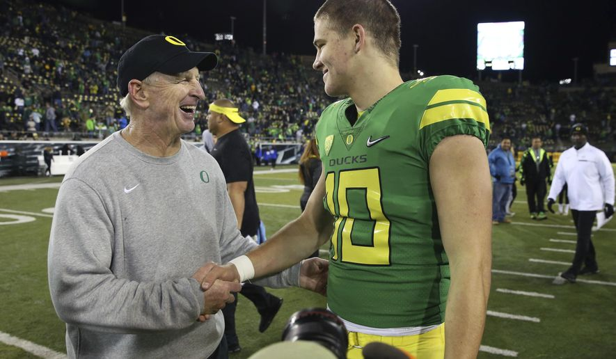 FILE - In this Nov. 18, 2017, file photo, Oregon defensive coordinator Jim Leavitt, left, congratulates quarterback Justin Herbert after the team's NCAA college football game against Arizona in Eugene, Ore. Florida State coach Willie Taggart is hiring former Oregon defensive coordinator Leavitt as an analyst to help fix a flailing defense, a person involved with the decision told The Associated Press on Wednesday night, Sept. 11, 2019. The person spoke on condition of anonymity because the hiring was still being finalized. Leavitt worked with Taggart in 2017 during the one season Taggart was head coach at Oregon. (AP Photo/Chris Pietsch, File)