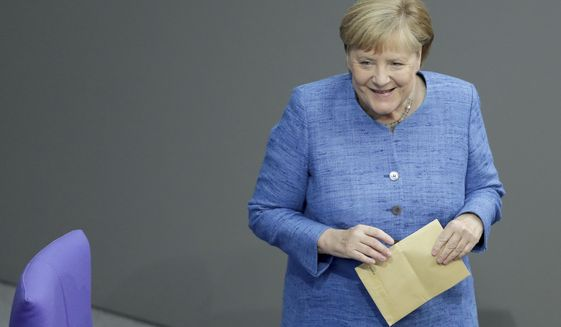 German Chancellor Angela Merkel holds an envelope as she arrives for a meeting of the German federal parliament, Bundestag, at the Reichstag building in Berlin, Germany, Wednesday, Sept. 11, 2019. (AP Photo/Michael Sohn)