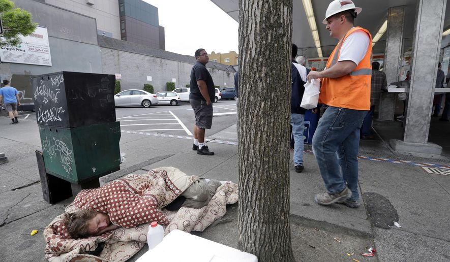 FILE - In this May 24, 2018 file photo, a man sleeps on the sidewalk as people behind line up to buy lunch at a Dick's Drive-In restaurant in Seattle. An elected official in King County, where Seattle is located, wants to dedicate $1 million for one-way bus tickets to relocate homeless people who say they want to reconnect with family outside the region. (AP Photo/Elaine Thompson, File)