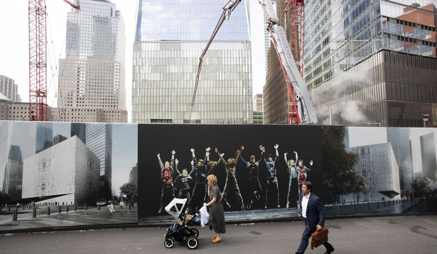People walk by murals promoting the future site of the Ronald O. Perelman Performing Arts Center as cranes work over the site at the World Trade Center, Monday, Sept. 9, 2019 in New York. The arts building is one of the final pieces to be completed as part of the reconstruction of the World Trade Center. Wednesday marks the 18th anniversary of the attacks of Sept. 11, 2001. (AP Photo/Mark Lennihan)