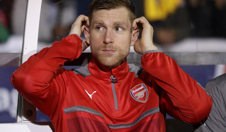FILE - In this Monday, Feb. 20, 2017 file photo Arsenal's Per Mertesacker watches from the bench during their English FA Cup fifth round soccer match against Sutton United at Gander Green Lane stadium in London. Arsenal academy head Per Mertesacker says on Wednesday, Sept. 11, 2019 there have been talks with players about the threat posed by gangs after Mesut Ozil and Sead Kolasinac had to fight off knife-wielding men. In an incident caught on camera in London last month, Kolasinac jumped out of a vehicle to confront the masked aggressors, who had pulled alongside the car on mopeds. (AP Photo/Matt Dunham, file)