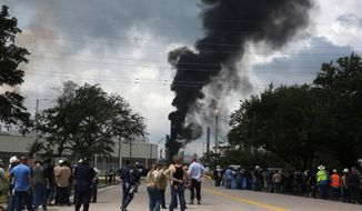 FILE - In this July 31, 2019, file photo, evacuated Exxon Mobil workers take a break or watch the fire from the Baytown Olefins Plant entrance in Baytown, Texas. Harris County will hire more environmental personnel for better response to dangerous chemical plant and refinery fires like several accidents this year near the Houston Ship Channel. The Houston Chronicle reports county commissioners Tuesday, Sept. 10, 2019, approved the $11.6 million plan for the 61 new hires and updated equipment for handling environmental emergencies. (Yi-Chin Lee/Houston Chronicle via AP, File)