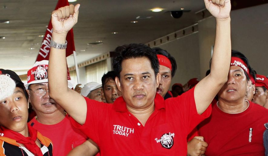 """FILE- in this April 11, 2009, file photo, anti-government leader Arisman Pongruangrong is cheered as he and others march through the 14th ASEAN Convention Center in Pattaya, Thailand. Thailand's Supreme Court has affirmed the prison sentences of 12 members of the """"Red Shirt"""" political movement on charges related to rioting that disrupted an important regional conference in 2009. (AP Photo/David Longstreath, File)"""