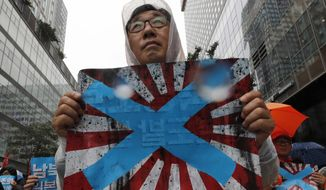 """FIEL - In this Aug. 15, 2019, file photo, South Korean protesters hold Japanese rising sun flags during a rally to mark the South Korean Liberation Day from Japanese colonial rule, in downtown Seoul, South Korea. South Korea has formally asked the International Olympic Committee to ban the Japanese """"rising sun"""" flag at next year's Tokyo Games, calling it a symbol of Japan's brutal wartime past. (AP Photo/Lee Jin-man, File)"""