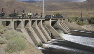 Federal officials walk across the Derby Dam in Wadsworth, Nev.,as Truckee River water flows beneath on Wednesday, Sept. 11, 2019 about 20 miles east of Reno, Nevada. The U.S. Bureau of Reclamation has launched a $23.5 million fish diversion project to help the threatened Lahontan cutthroat trout pass upstream to their native spawning grounds cutoff since the dam was built in 1905. Before that, the trout would migrate from Pyramid Lake in the high desert 120 miles upstream to spawn in Lake Tahoe. (AP Photo/Scott Sonner)