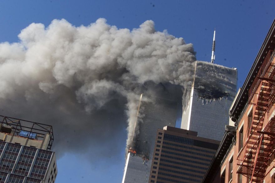 In this Sept. 11, 2001, file photo, smoke rises from the burning twin towers of the World Trade Center after hijacked planes crashed into the towers in New York City. (AP Photo/Richard Drew, File)