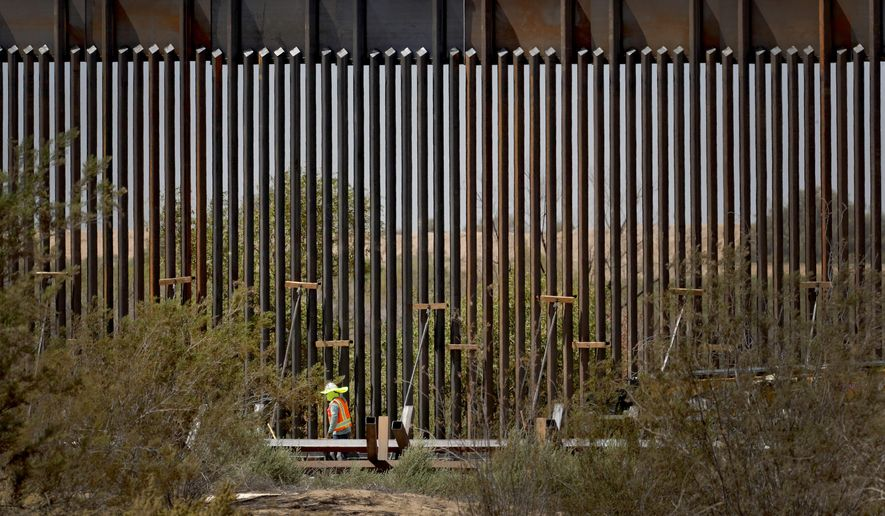 A government contractor walks beside a completed section of Pentagon-funded border wall along the Colorado River, Tuesday, Sept. 10, 2019, in Yuma, Ariz. The 30-foot high wall replaces a five-mile section of Normandy barrier and post-n-beam fencing along the International border that separates Mexico and the United States. Construction began as federal officials revealed a list of Defense Department projects to be cut to pay for President Donald Trump's wall. (AP Photo/Matt York) ** FILE **
