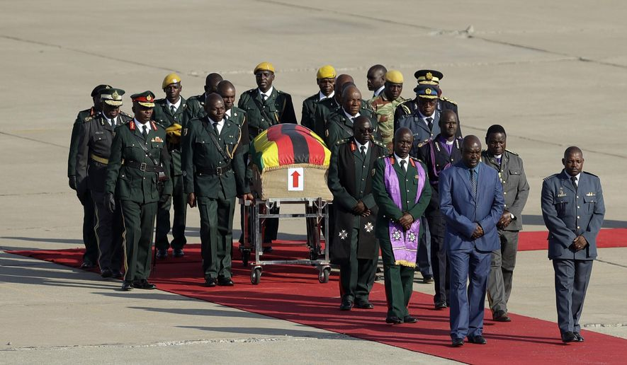A coffin carrying the remains of Zimbabwe's longtime ruler Robert Mugabe arrives from Singapore, at Robert Gabriel Mugabe International Airport in Harare, Zimbabwe, Wednesday, Sept. 11, 2019. The body of Mugabe is being flown to the capital, Harare, on Wednesday where it will be displayed at historic locations for several days before burial at a location still undecided because of friction between the ex-leader's family and the government. AP Photo/Themba Hadebe)
