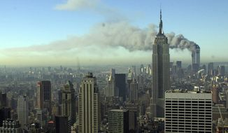 Plumes of smoke pour from the World Trade Center buildings in New York Tuesday, Sept. 11, 2001. Planes crashed into the upper floors of both World Trade Center towers minutes apart Tuesday in a horrific scene of explosions and fires that left gaping holes in the 110-story buildings. (AP Photo/Patrick Sison)
