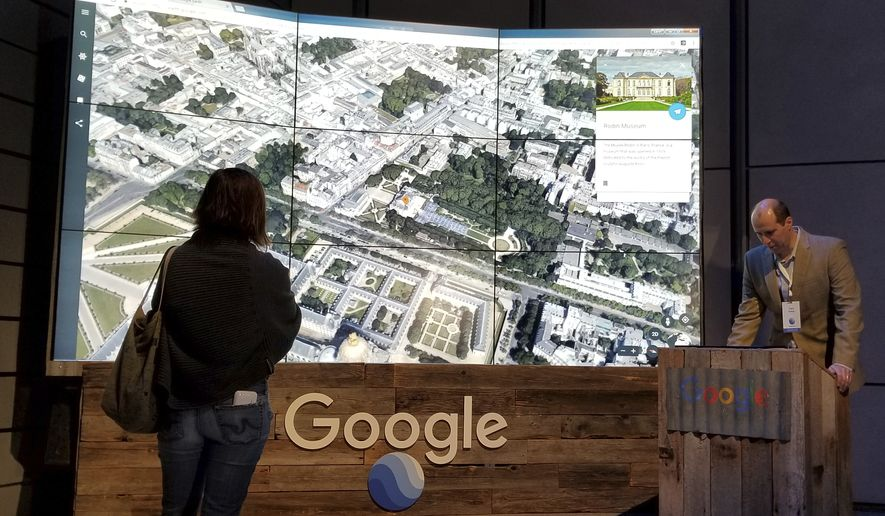 Sean Askay, right, engineering manager with Google Earth, demonstrates features on Google Earth, displayed in background, Tuesday, April 18, 2017, in New York. Google Earth is getting a revival, with the mapping service becoming more of a tool for adventure and exploration. (AP Photo/Anick Jesdanun)