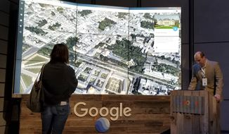 Sean Askay, right, engineering manager with Google Earth, demonstrates features on Google Earth, displayed in background, Tuesday, April 18, 2017, in New York. Google Earth is getting a revival, with the mapping service becoming more of a tool for adventure and exploration. (AP Photo/Anick Jesdanun) **FILE**