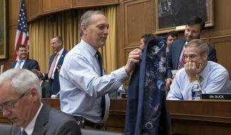 Rep. Andy Biggs, R-Ariz., the newly elected chairman of the conservative House Freedom Caucus, takes off his jacket for the amusement of fellow caucus member Rep. Jim Jordan, R-Ohio, right, as they arrive for the start of a markup session of the House Judiciary Committee as they work on guidelines for impeachment hearings on President Donald Trump, at the Capitol in Washington, Thursday, Sept. 12, 2019. (AP Photo/J. Scott Applewhite)