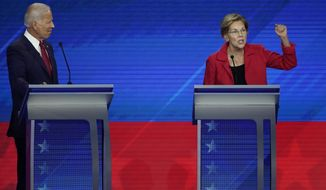 Former Vice President Joe Biden, left, listens as Sen. Elizabeth Warren, D-Mass., right, speaks Thursday, Sept. 12, 2019, during a Democratic presidential primary debate hosted by ABC at Texas Southern University in Houston. (AP Photo/David J. Phillip)
