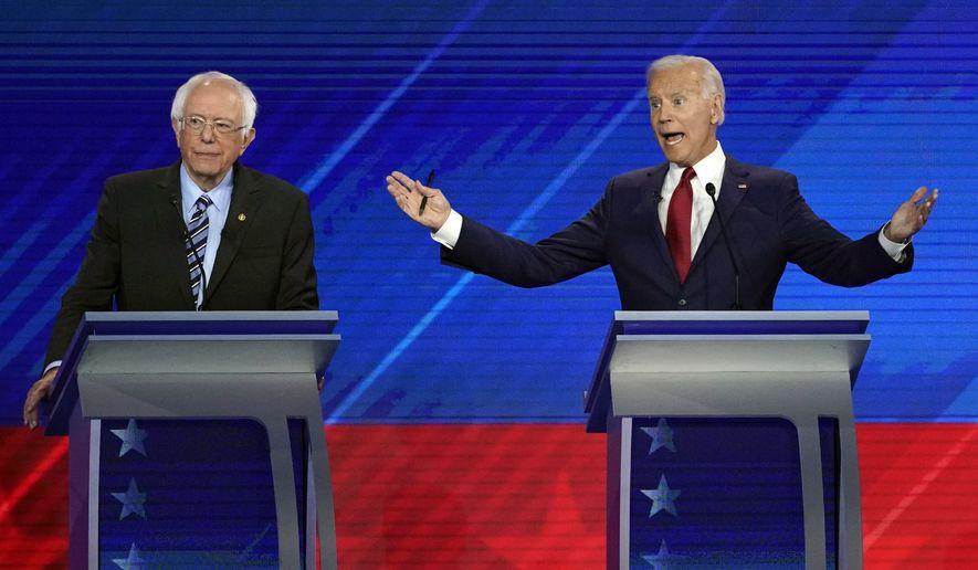 Sen. Bernie Sanders, I-Vt., left, listens as former Vice President Joe Biden, right, speaks Thursday, Sept. 12, 2019, during a Democratic presidential primary debate hosted by ABC at Texas Southern University in Houston. (AP Photo/David J. Phillip)