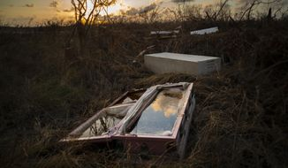A shattered and water-filled coffin lays exposed to the elements in the aftermath of Hurricane Dorian, at the cemetery in Mclean's Town, Grand Bahama, Bahamas, Wednesday Sept. 11, 2019. Bahamians are tackling a massive clean-up a week after Hurricane Dorian devastated the archipelago's northern islands. (AP Photo/Ramon Espinosa)