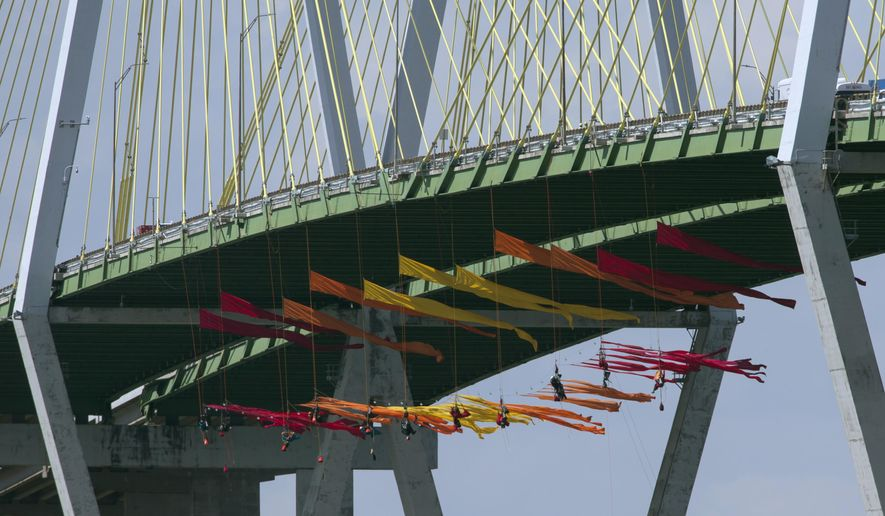 Greenpeace USA protesters dangle from the Fred Hartman Bridge Thursday, Sept. 12, 2019, in Baytown, Texas. A portion of the Houston Ship Channel has closed after about a dozen Greenpeace USA activists protesting the use of fossil fuels suspended themselves from a bridge ahead of a Democratic presidential debate.( Yi-Chin Lee/Houston Chronicle via AP)