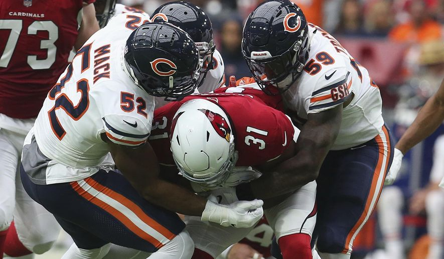 FILE - In  this Sept. 23, 2018, file photo, Chicago Bears linebacker Khalil Mack (52) makes a tackle on Arizona Cardinals running back David Johnson (31) with help from Danny Trevathan (59) during the first half of an NFL football game in Glendale, Ariz. Trevathan returns with the Bears on Sunday, Sept. 15, 2019, to Denver, where he played from 2012-15 and won a Super Bowl. (AP Photo/Ralph Freso, File)