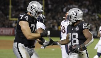 Oakland Raiders running back Josh Jacobs, right, is greeted by offensive tackle Kolton Miller (74) after scoring a touchdown during the first half of an NFL football game against the Denver Broncos Monday, Sept. 9, 2019, in Oakland, Calif. (AP Photo/Ben Margot)