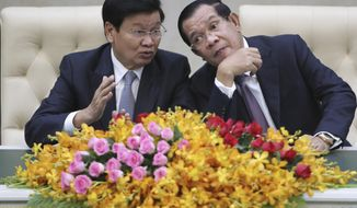 Cambodian Prime Minister Hun Sen, right, talks with his Laos counterpart Thonloun Sisoulith, left, as they witness to a signing ceremony in Phnom Penh, Cambodia, Thursday, Sept. 12, 2019. Thonloun Sisoulith is on his two-day official visit to Cambodia. (AP Photo/Heng Sinith)
