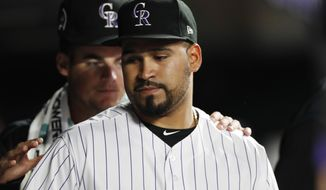 Colorado Rockies starting pitcher Antonio Senzatela, front, is congratulated by pitcher Peter Lambert after Senzatella was replaced for a pinch-hitter during the sixth inning of a baseball game against the St. Louis Cardinals on Wednesday, Sept. 11, 2019, in Denver. (AP Photo/David Zalubowski)