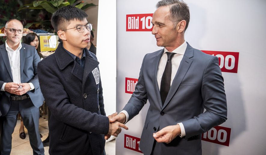 German Foreign Minister Heiko Maas, right, and Hong Kong activist Joshua Wong, left, shake hands during a reception of a German news paper in Berlin, Germany, Monday, Sept. 9, 2019. Wong will address the media during a press conference in Berlin on Wednesday, Sept. 11, 2019. (Michael Kappeler/dpa via AP)