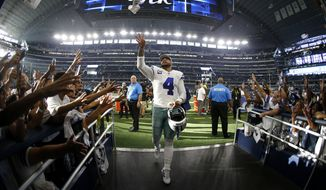 Dallas Cowboys' Dak Prescott (4) tosses a item to fans as he walks into the team tunnel after their NFL football game against the New York Giants in Arlington, Texas, Sunday, Sept. 8, 2019. The Cowboys won 35-17. (AP Photo/Ron Jenkins)