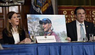 FILE - In this Jan. 29, 2019, file photo, Linda Beigel Schulman, left, holds a photograph of her son Scott Beigel, who was killed during the Valentine's Day massacre at Marjory Stoneman Douglas High School, while speaking with New York Gov. Andrew Cuomo and gun safety advocates during a news conference at the state Capitol in Albany, N.Y. The waiting period on certain New York gun purchases has been extended from three days to 30 days under a new state law. The measure approved by Gov. Andrew Cuomo went into effect Thursday, Sept. 12, 2019. (AP Photo/Hans Pennink, File)