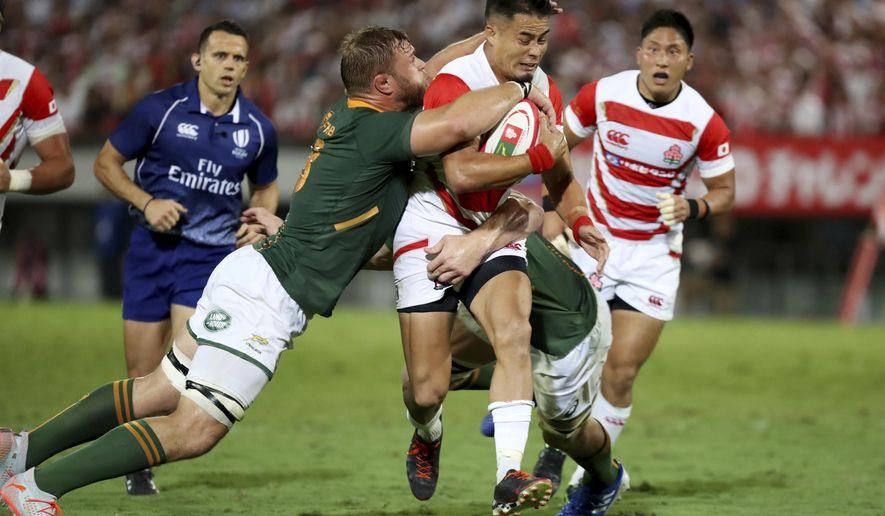 Japan's Yu Tamura (10) runs against South Africa's Duane Vermeulen (8) during a rugby match at Kumagaya Rugby Stadium Friday, Sept. 6, 2019, in Saitama, Japan. (AP Photo/Eugene Hoshiko)