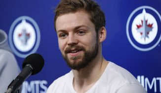 FILE - In this April 22, 2019, file photo, Winnipeg Jets' Josh Morrissey speaks to media at their closing press conference after losing in the first round of the NHL playoffs, in Winnipeg, Manitoba. The Winnipeg Jets have signed defenseman Josh Morrissey to an eight-year, $50 million contract extension. The Jets announced the move on Thursday, Sept. 12, 2019, one day before the start of training camp. (John Woods/The Canadian Press via AP, File)
