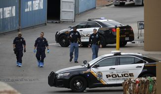 In this Aug. 6, 2019, file photo, police officers walk behind a Walmart at the scene of a mass shooting at a shopping complex in El Paso, Texas. Patrick Crusius, 21, was indicted Thursday, Sept. 12, 2019, for capital murder in connection with the Aug. 3 mass shooting that left 22 dead. He is jailed without bond. (AP Photo/John Locher, File)