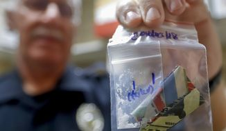 In this Sept. 11, 2019, photo, narcotics detective Will Pfeiffer shows a stored evidence bag that containing methamphetamine before it is destroyed in Barberton, Ohio. The tentative settlement involving the opioid crisis and the maker of OxyContin could mean that thousands of local governments will one day be paid back for some of the costs of responding to the epidemic. (AP Photo/Keith Srakocic)