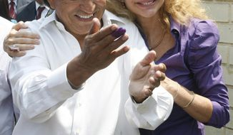 FILE - In this April 10, 2011 file photo Presidential candidate Alejandro Toledo, accompanied by his wife Eliane Karp, greet supporters outside a polling station after casting his ballot in the general elections in Lima, Peru. A federal judge in San Francisco has denied bail to former Peruvian President Toledo in an extradition hearing that ended with an emotional outburst by his wife who had to be dragged out of the courtroom after she started shouting at prosecutors. (AP Photo/Juan Diego Contreras,File)