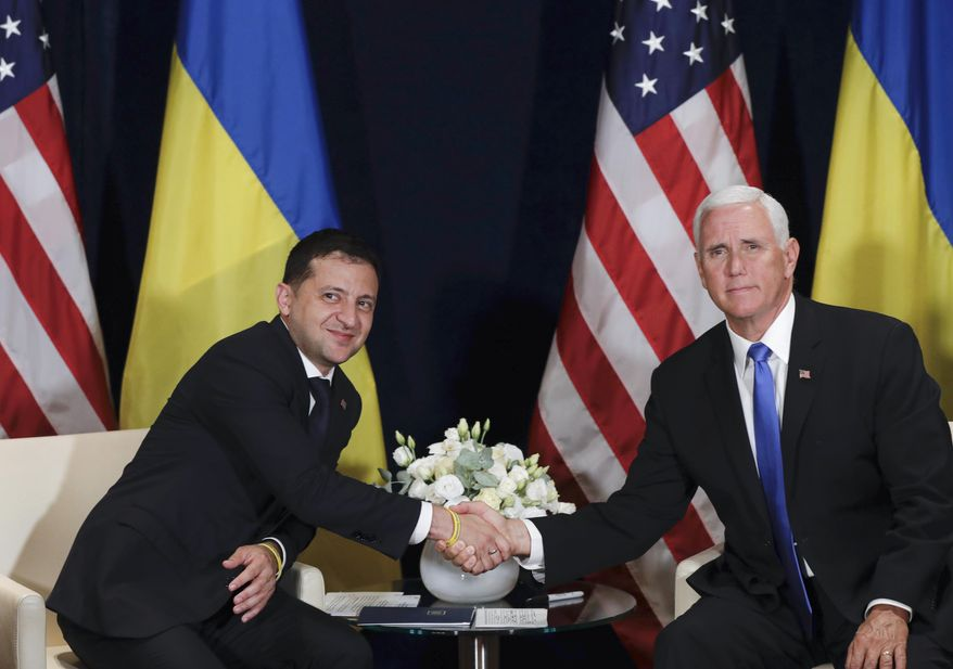 Ukraine's President Volodymyr Zelenskiy, left, shakes hands with U.S. Vice President Mike Pence, in Warsaw, Poland, Sunday, Sept. 1, 2019. (AP Photo/Petr David Josek)