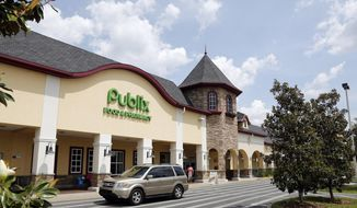 In this Sunday, May 19, 2013, file photo, a vehicle passes the front of the Publix supermarket in Zephyrhills, Fla.  Publix Supermarkets is joining a growing number of retailers in asking customers not to openly carry firearms in its stores, even if state laws allow it. (AP Photo/Scott Iskowitz, File)