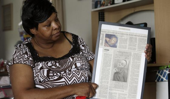 In this photo taken Tuesday, Aug. 6, 2019 Brenda Scurlock is shown in her home in Lumber Bridge, N.C. holding a newspaper clipping about her son's murder. Scurlock's son Avery Scurlock, who used the name Chanel when dressing as a woman in social settings and hoped to have sex reassignment surgery,  was found shot to death in June. This death of a transgender person in North Carolina is one of 18  so far this year, and  17  of the victims have been black women. (AP Photo/Gerry Broome)