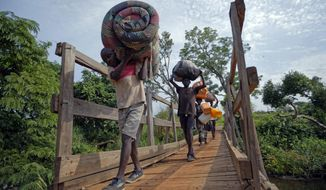 """FILE - In this Thursday, June 8, 2017 file photo, from left, South Sudanese refugees Thomas Wani, 12, brother Peter Lemi, 14, mother Rose Sunday, and father Julius Lezu, cross a wooden bridge from South Sudan to Uganda at the Busia crossing, near Kuluba, in northern Uganda. The representative of the United Nations refugee agency in Uganda says """"major gaps"""" in funding are constraining their work in the East African country sheltering 1.3 million refugees. Joel Boutroue told reporters in the Ugandan capital, Kampala, on Thursday, Sept. 12, 2019 that UNHCR in Uganda is operating at only 35% of the total requirements.(AP Photo/Ben Curtis, File)"""