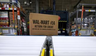 In this Nov. 9, 2018, file photo, a box of merchandise is unloaded from a truck and sent along a conveyor belt at a Walmart Supercenter in Houston. Walmart is rolling out an unlimited grocery delivery subscription service this fall for a $98 annual fee. The service will reach 1,400 stores in 200 markets and allows the nation's largest grocer to further tap into time-starved shoppers looking for convenience. (AP Photo/David J. Phillip, File)