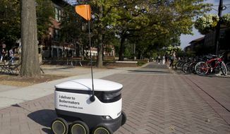 A Starship Technologies robot drives through campus delivering food at Purdue University, Thursday, Sept. 12, 2019, in West Lafayette, Ind. For the past month, Purdue students have seen little robots making their way across campus, down sidewalks and across streets. They're white and cooler-sized, with six little wheels and a long pole with an orange flag alerting those around of their presence. (Nikos Frazier/Journal & Courier via AP)