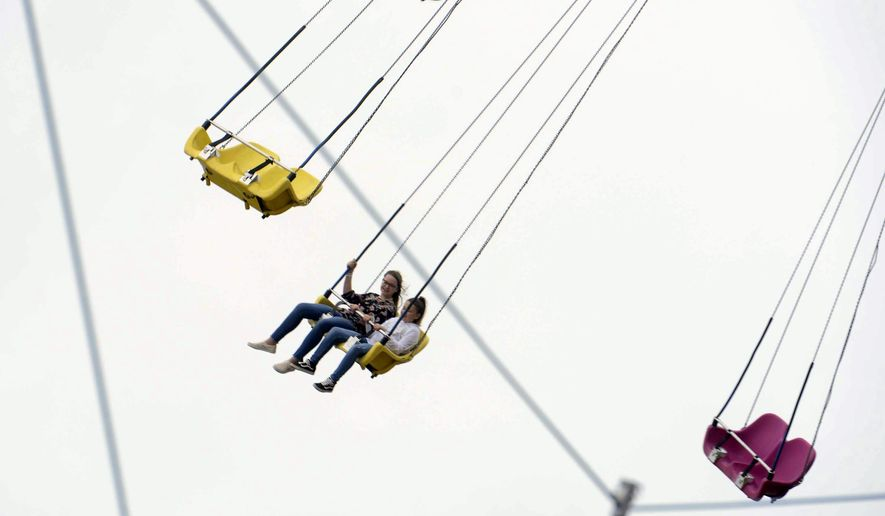 In this file photo, people enjoy the rides at the annual Danville-Pittsylvania County Fair in Ringgold, Va., which opened Friday, Sept. 13, 2019. A California man has been arrested for phoning in a fake mass-shooting threat about a local county fair, apparently in an attempt to get out of attending the event with his family. (Caleb Ayers/Danville Register & Bee via AP) **FILE**