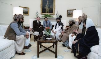 """In this photo courtesy of the Ronald Reagan Library, then-President Ronald Reagan meets with Afghan """"freedom fighters"""" on Feb. 2, 1983, in the Oval Office of the White House in Washington, to discuss Soviet atrocities in Afghanistan. The Taliban did not emerge until 1994. A Twitter user posted the photo on Sept. 7, 2019, with a caption implying that Reagan met with the Taliban: """"NeverTrumpers: A President meeting with the Taliban, this is horrific!"""" The miscaptioned photo circulated prominently on Twitter and Facebook after it was revealed that President Donald Trump planned to meet with Taliban leaders and Afghan officials at the presidential retreat in Camp David, Maryland, just days before the 9/11 anniversary. (Courtesy Ronald Reagan Library via AP) ** FILE **"""