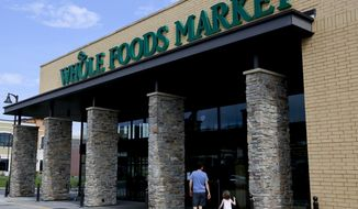 In this Aug. 8, 2018, photo shoppers enter a Whole Foods Market in Upper Saint Clair, Pa. Whole Foods, the grocery chain owned by Amazon, is cutting health care benefits for its part-time workers, a move that could leave about 1,900 of its employees without medical coverage. Starting next year, Whole Foods employees have to work at least 30 hours a week to qualify for its health care benefits, up from the 20 hours a week it currently requires. (AP Photo/Gene J. Puskar, File)