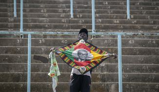A man in the stands holds a banner with the face of former president Robert Mugabe, as members of the public queue up to view his body at the Rufaro stadium in the capital Harare, Zimbabwe Friday, Sept. 13, 2019. The ongoing uncertainty of the burial of Mugabe, who died last week in Singapore at the age of 95, has eclipsed the elaborate plans for Zimbabweans to pay their respects to the former guerrilla leader at several historic sites. (AP Photo/Ben Curtis)