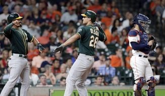 Oakland Athletics Marcus Semien, left, and Matt Olson, center, celebrate at the plate next to Houston Astros catcher Robinson Chirinos, right, after they scored on a two-run home run by Olson during the third inning of a baseball game Thursday, Sept. 12, 2019, in Houston. (AP Photo/Michael Wyke)