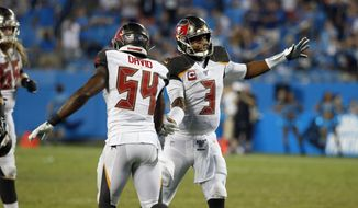 Tampa Bay Buccaneers outside linebacker Lavonte David (54) and quarterback Jameis Winston (3) celebrate following the team's 20-14 win over the Carolina Panthers following an NFL football game in Charlotte, N.C., Friday, Sept. 13, 2019. (AP Photo/Brian Blanco)