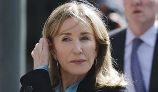 In this April 3, 2019, file photo, actress Felicity Huffman arrives at federal court in Boston to face charges in a nationwide college admissions bribery scandal. Huffman, who pleaded guilty to a single count of conspiracy and fraud in May, is returning for sentencing in federal on Friday, Sept. 13, 2019, court in Boston. (AP Photo/Charles Krupa, File)