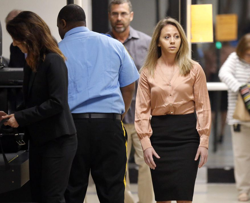 CORRECTS DATE TO SEPT. 13 -Fired Dallas police Officer Amber Guyger, right, arrives for jury selection in her murder trial at the Frank Crowley Courthouse in downtown Dallas, Friday, Sept. 13, 2019. Guyger shot and killing Botham Jean, an unarmed man in his own apartment last year. (Tom Fox/The Dallas Morning News via AP)