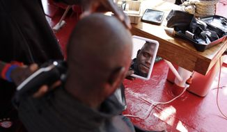 Mouctar Diallo, from Guinea, looks at himself in the mirror as he gets his hair shaved aboard the Ocean Viking humanitarian rescue ship, in the Mediterranean Sea, Friday, Sept. 13, 2019. Diallo was rescued at sea on Sept. 8, his birthday, by the Ocean Viking in his fifth attempt to reach Europe from Libya. (AP Photo/Renata Brito)