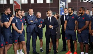 France's President Emmanuel Macron, center, speaks to French national rugby team players ahead of the upcoming Rugby Wcup, at the National Rugby Center in Marcoussis, south of Paris, Thursday, Sept.5, 2019. The French rugby team is preparing for the upcoming 2019 World Cup in Japan. (AP Photo/Christophe Ena, Pool)