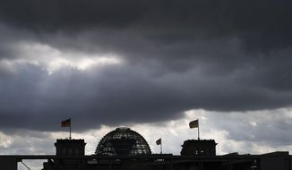 Dark clouds cover the sky over the Reichstag building in Berlin, Germany, Friday, Sept. 13, 2019. The German government says the country's economy is in a weak phase but it doesn't currently see indications it will enter a long-term recession. (AP Photo/Markus Schreiber)